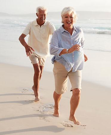 senior-retired-couple-running-along-summ