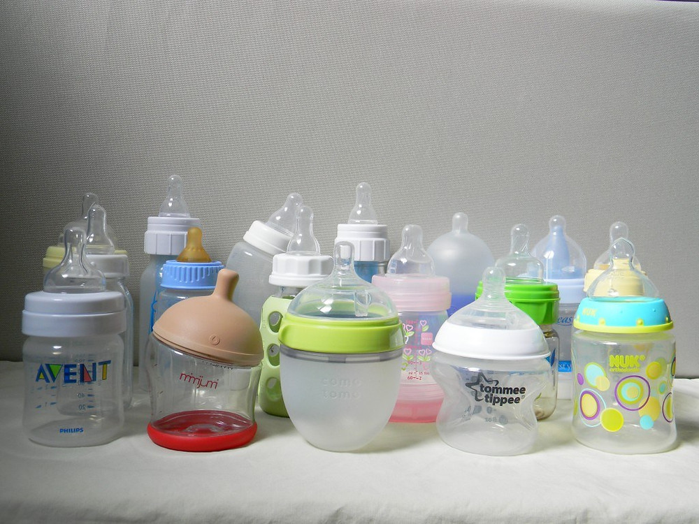 various baby bottles sitting on benchtop being exposed to germs and bacteria
