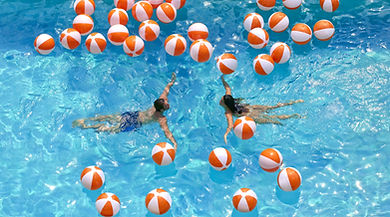 Boy and girl swimming in a large pool with orange and white balls