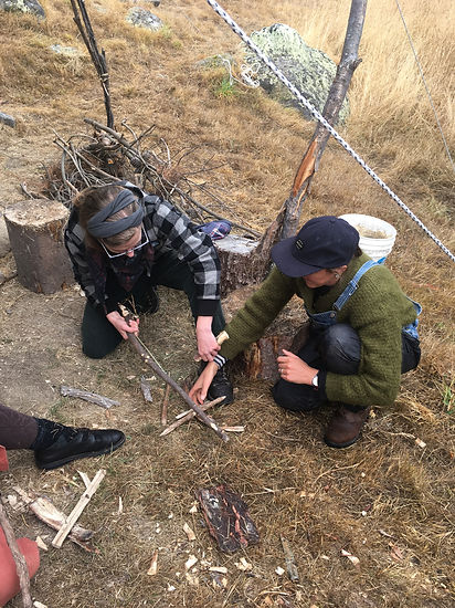 Two adults learning how to use a bow-drill to make fire from scratch.
