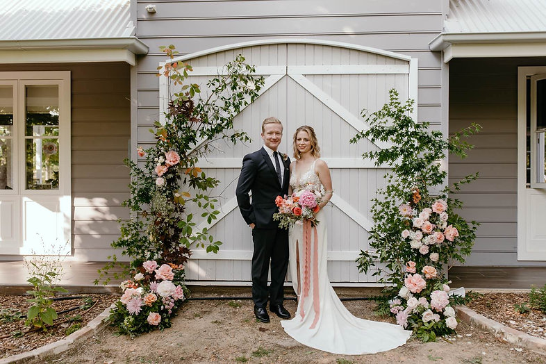natural style asymmetical floral arch for barn wedding