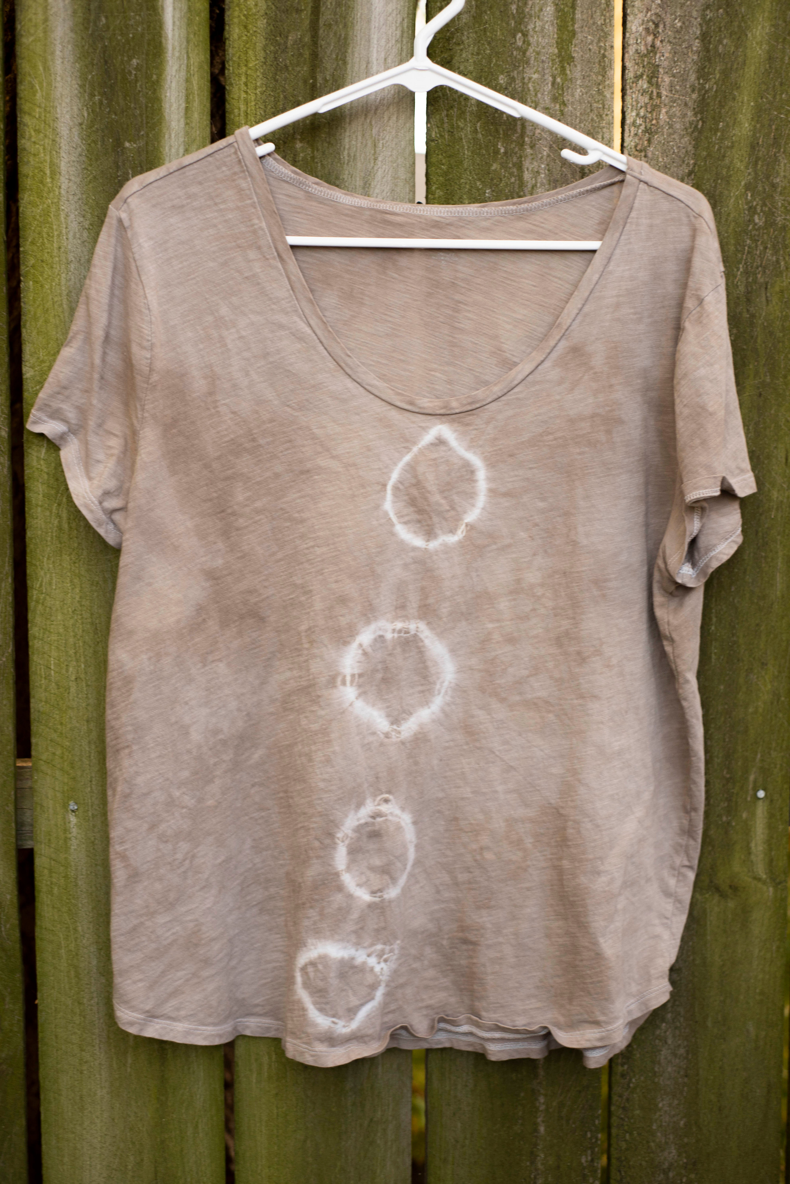 A brown tee shirt with four organic shaped circles down the front.
