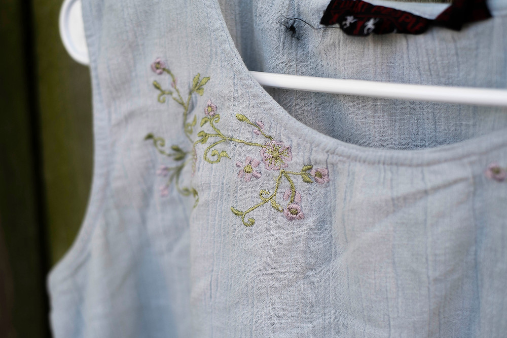 A close up photo of floral embroidery on a light purple shirt.