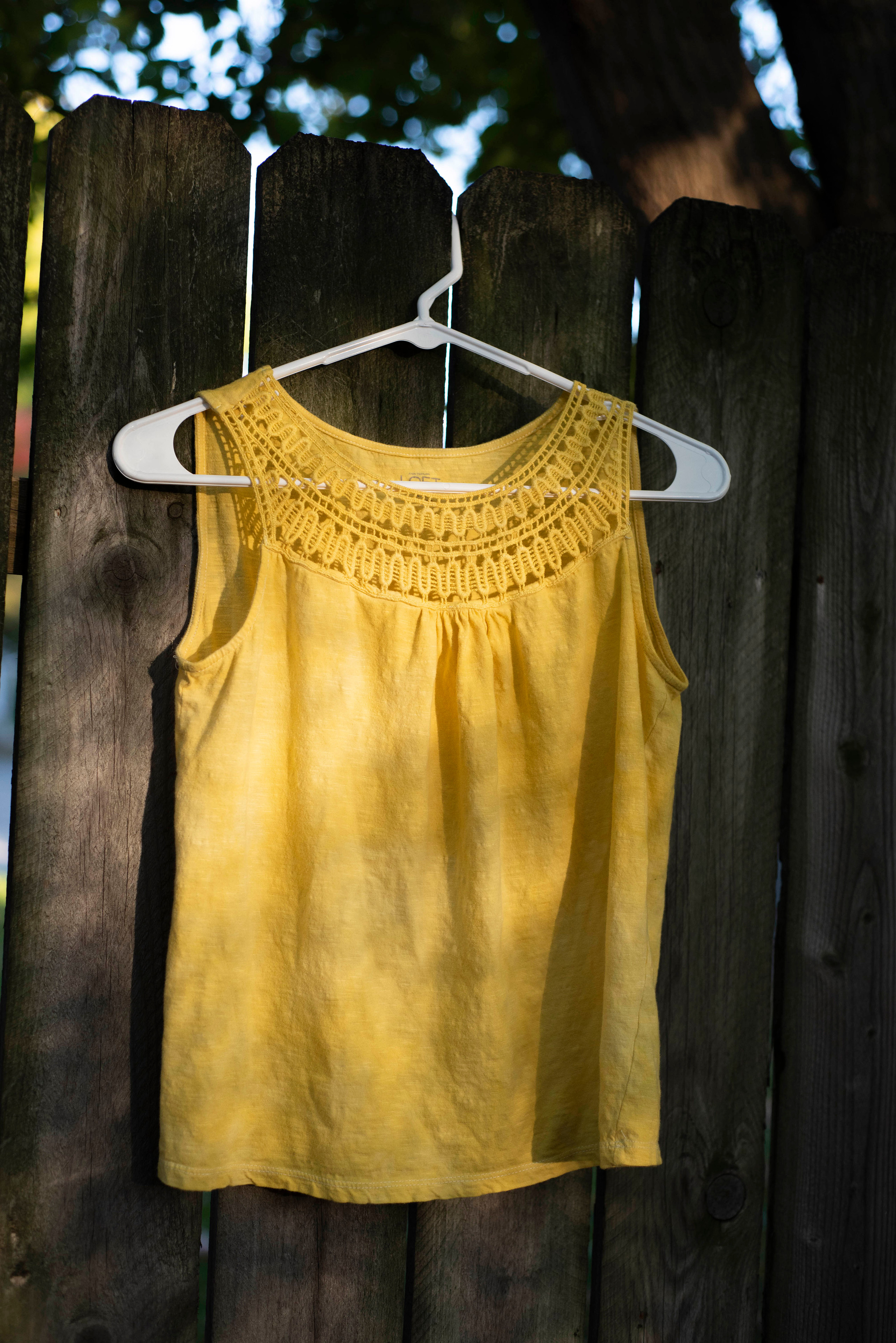A yellow tank top with a lacy pattern around the top crew neck and straps.