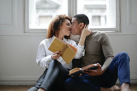 couple-kissing-while-holding-books-39670