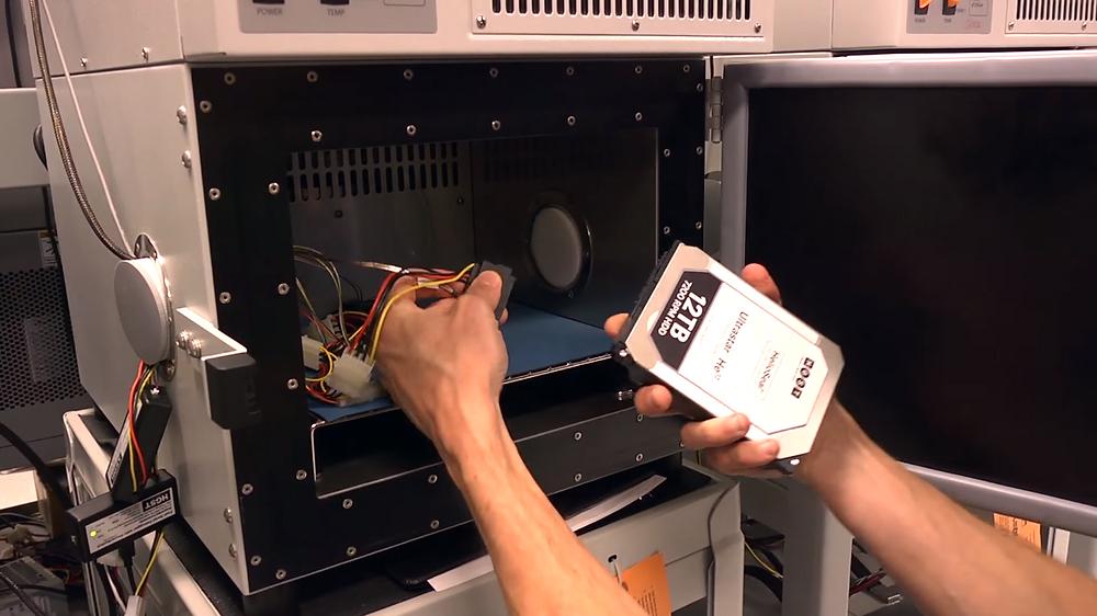 """Một HDD 3.5"""" SAS Ultrastar He12 dung lượng 12TB đang được kỹ sư của WD kết nối với cáp SAS SFF-8482 để tiến hành thử nghiệm."""