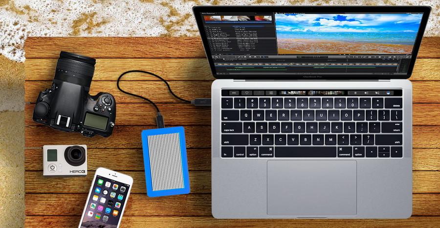 Ổ đĩa gắn ngoài CalDigit Tuff kết nối với máy tính MacBook Pro qua cáp USB-C.