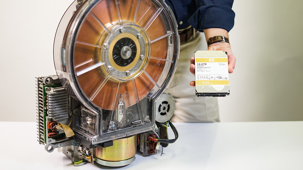 Một HDD IBM 14 inch từ đầu những năm 1980 bên cạnh HDD 3.5 inch dung lượng lớn nhất hiện nay.