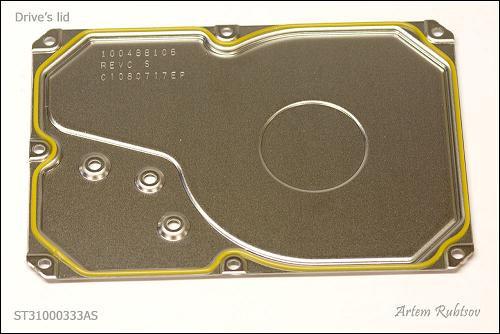 Phần nắp (lid) của HDD không có gì đặc biệt, chỉ là một miếng thép không gỉ và sợi dây cao su để ngăn bụi.