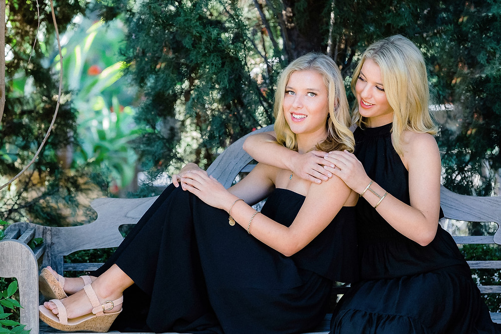 twin sisters embracing sitting on a bench
