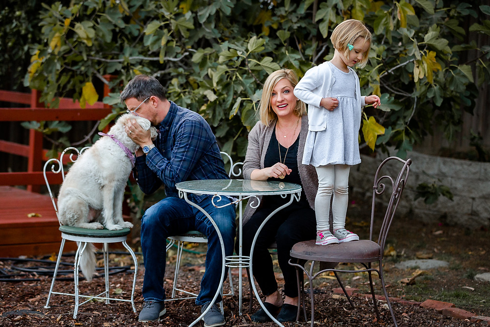 lifestyle family photo session. dad kissing white fluffy dog on its head, mom smiles while little blond girl stands on a chair
