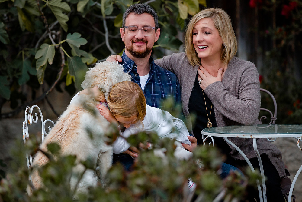 little blond girl hugging her white fluffy dog during a lifestyle family photo session while mom and dad look on with heart-felt emotion