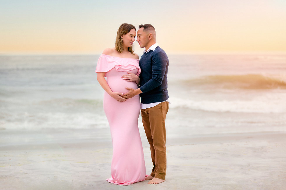 pregnant woman and husband embracing on a beach