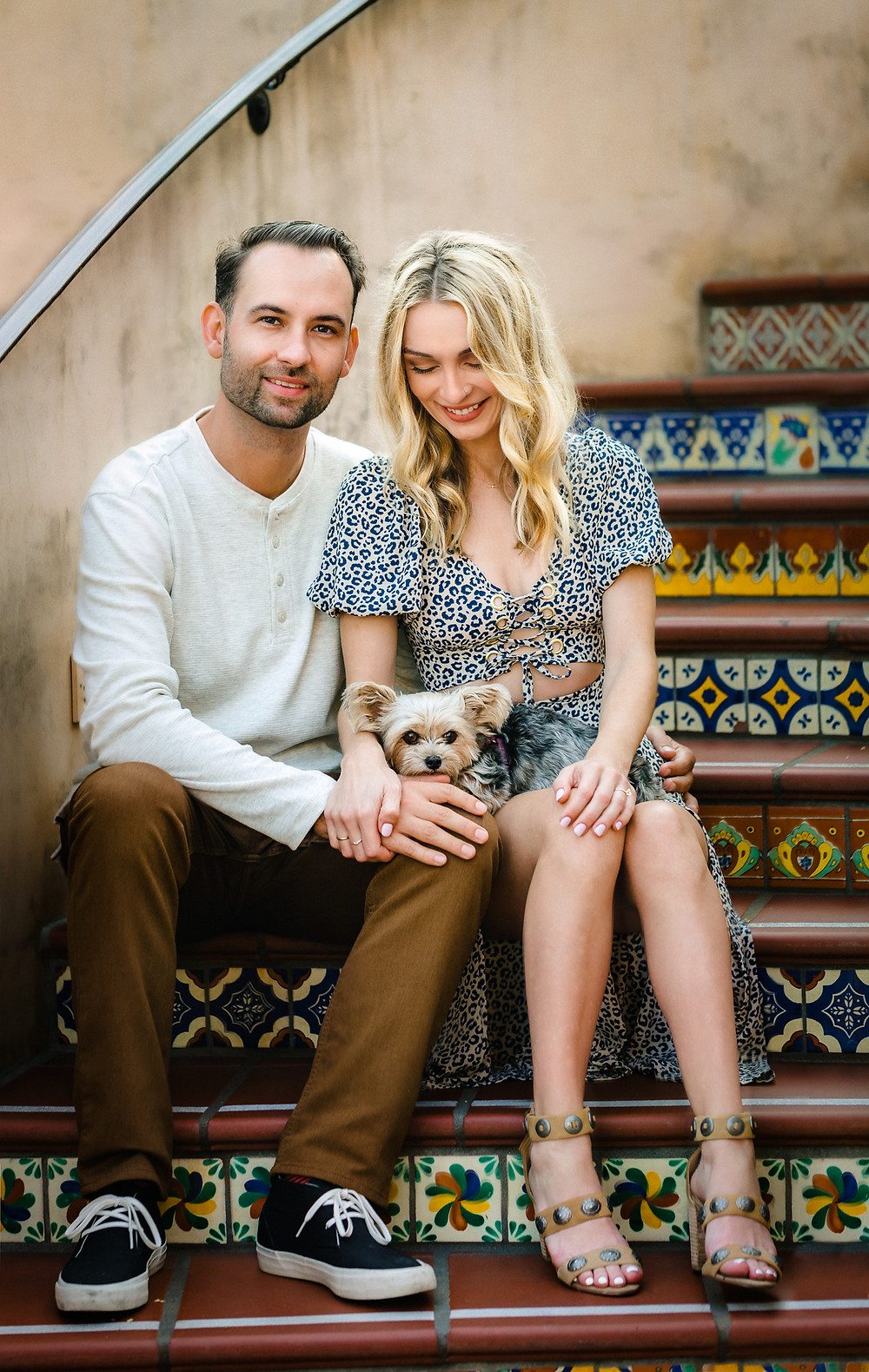 couple with their yorkie dog sitting next to each other on the spanish tiled steps of the Brisas Del Mar, Inn at the Beach