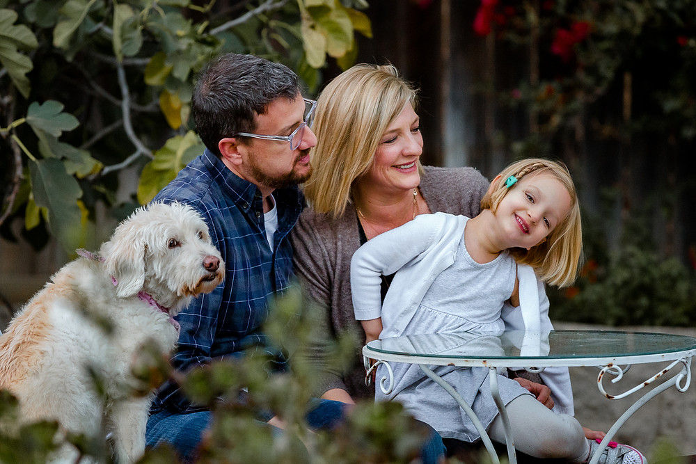 Mom and dad look at little girl smiling  during a lifestyle family photo session while white fluffy dog looks at the camera