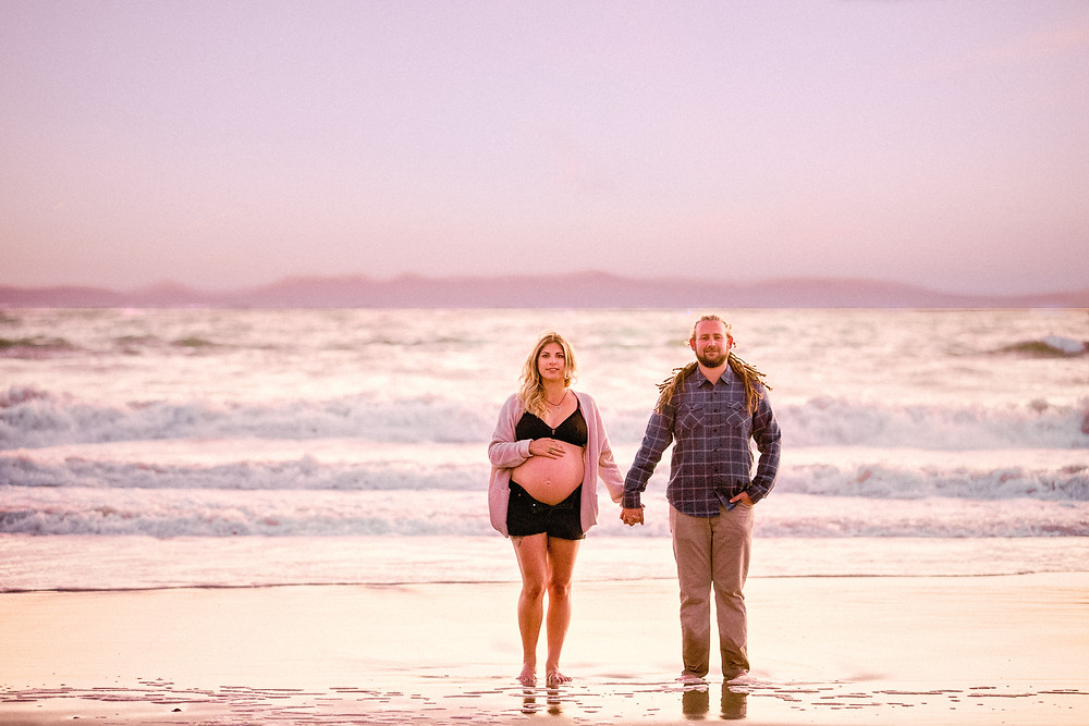 maternity photos with a woman and man at the beach
