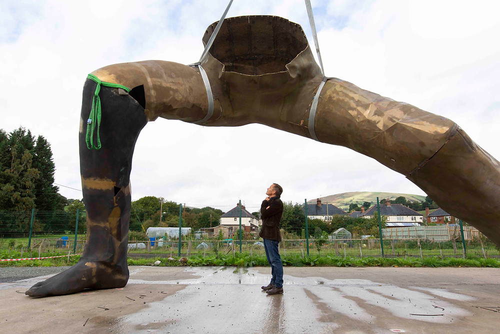 Artist Joseph Hillier standing underneath the legs of his enormous sculpture