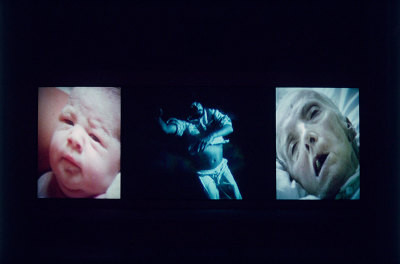 Photo of video display showing a baby, man and old person