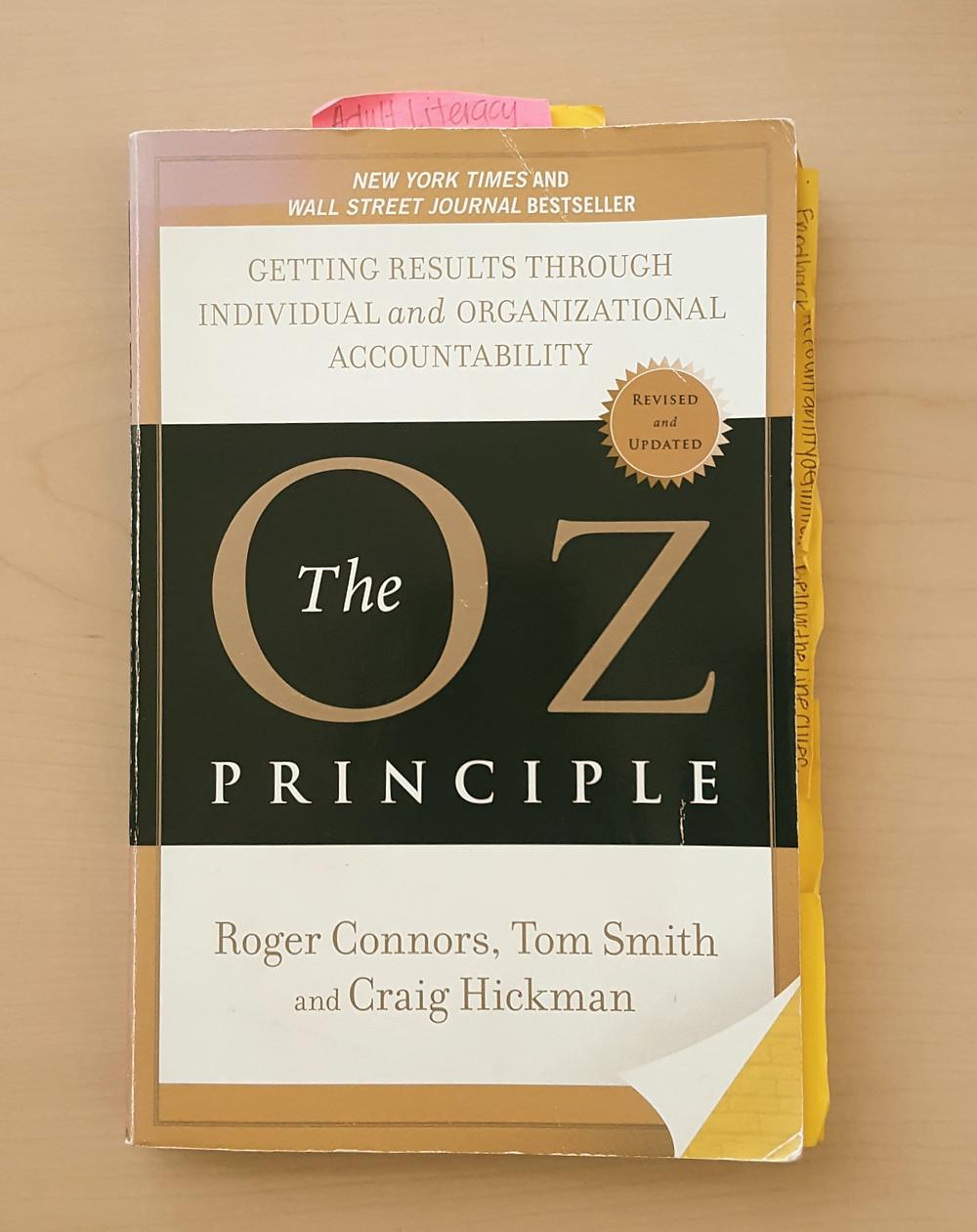 The Oz Principle book on a wooden desk