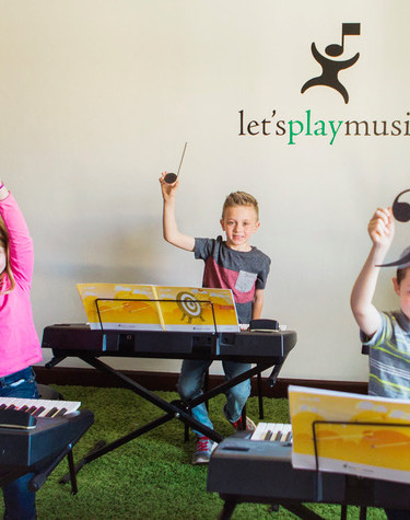 LPM kids at piano holding staff pieces.j