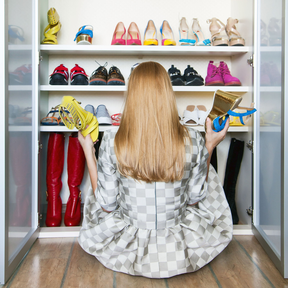 woman sitting in front of her shoe closet