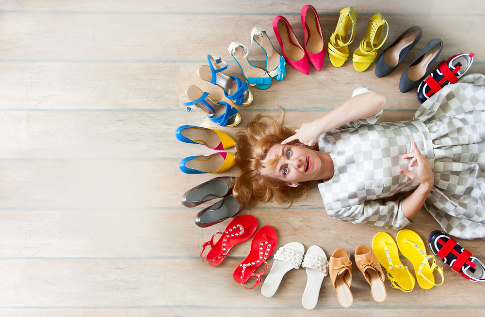 person laying on the ground with shoes all around