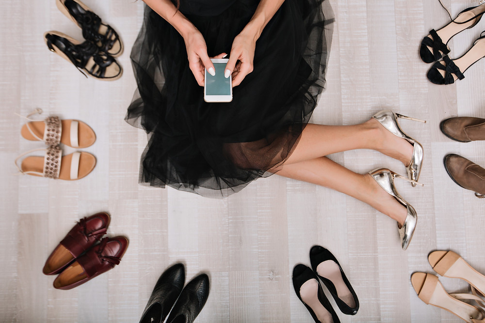 person sitting on the floor with shoes and a phone in hand