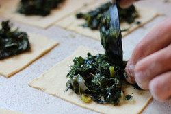 Preparing pitarakia with greens
