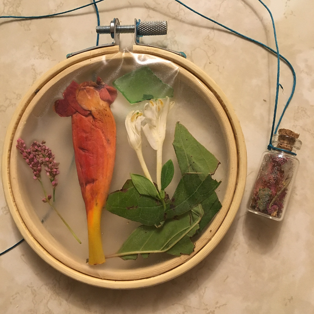 Flowers and leaves inside an embroidery hoop and a tiny glass bottle of rose petals and dandelion fluff