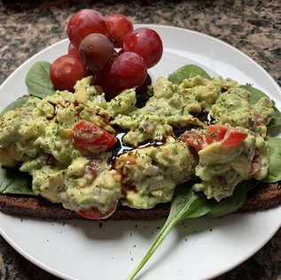 Avocado Toast w/cherry tomatoes, red onions, on a bed of baby spinach, and splashed with balsamic vinegar