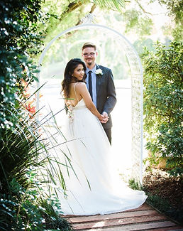 bride and groom in garden archway for wedding