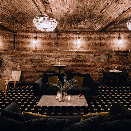 Lounge seating in brick room with warm lighting and black and white tile floors