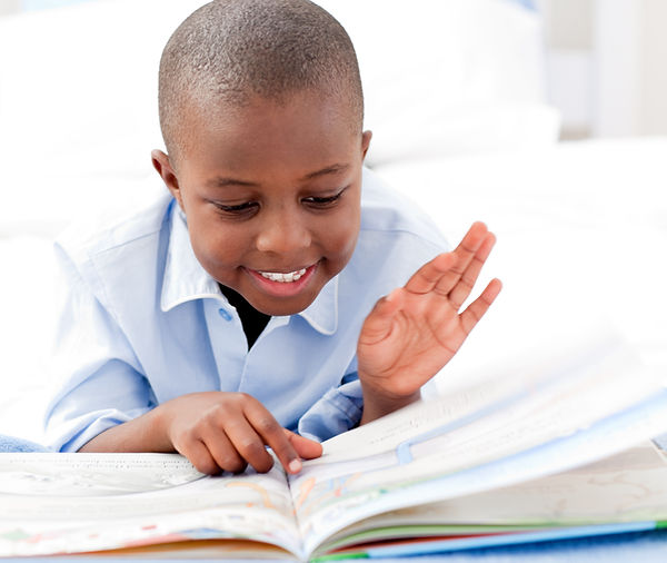 Small boy reading a book on his bed.jpg