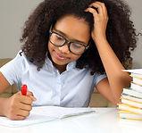 schoolgirl with glasses doing homework.