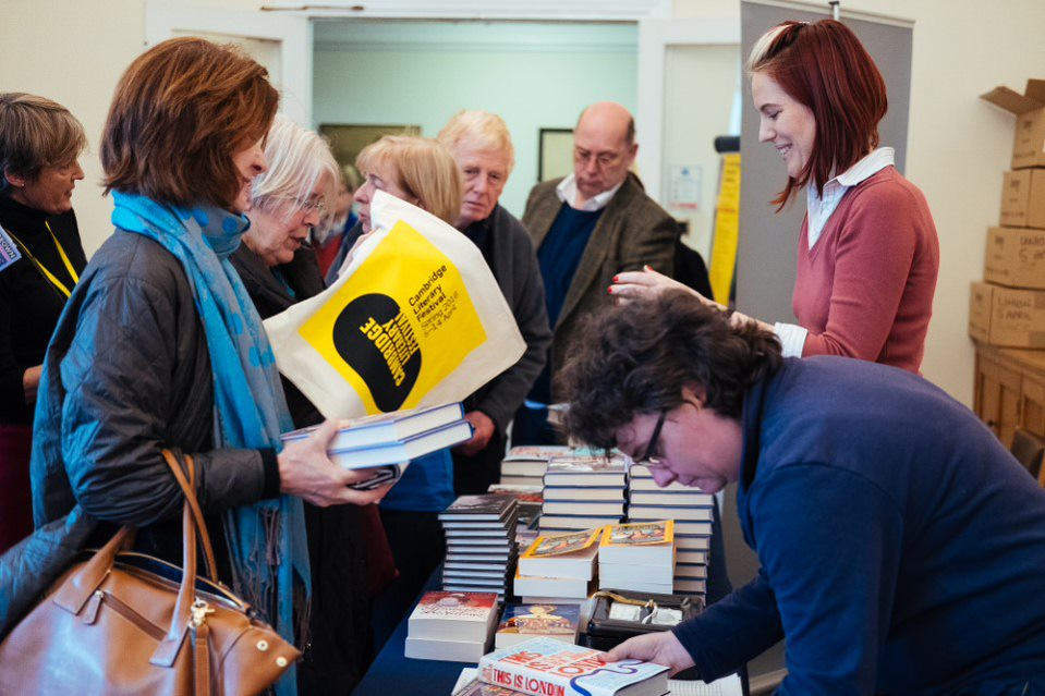 Book sales crowd with smiling seller spr