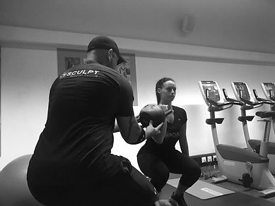 Personal trainer showing client how to use kettlebells for core stability and weight loss.