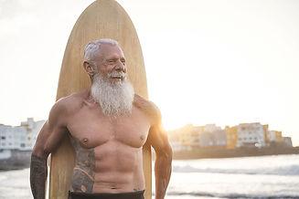 tattooed-senior-surfer-holding-vintage-surf-board-2021-04-14-22-48-32-utc.jpg
