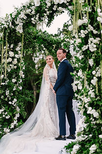 Bride and Groom under a lush chuppah holding hands looking out at their guests and about to say I do