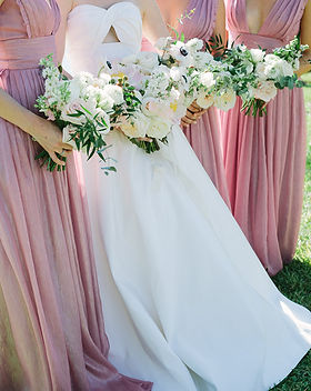 Bride and Bridesmaides. The bridesmaides are in muted pink dresses and holding small bouquets with roses and greenery.