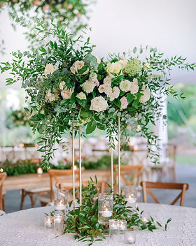 Tal centerpiece with gold frame holding up the floral arrangement that has roses and greenery.