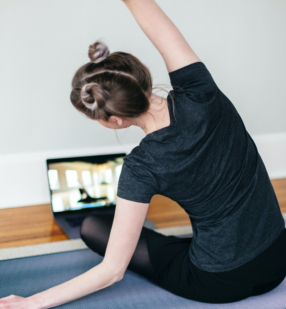 Young women stretching with online lesson