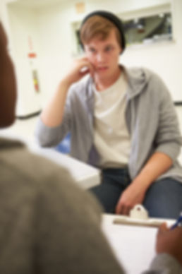 Young Man Talking To Counsellor about behaviour