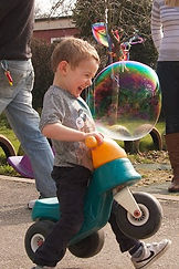 child chases a big bubble, smiling and riding a tricycle