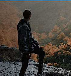 Man Looking Out From On Top Of A Mountain