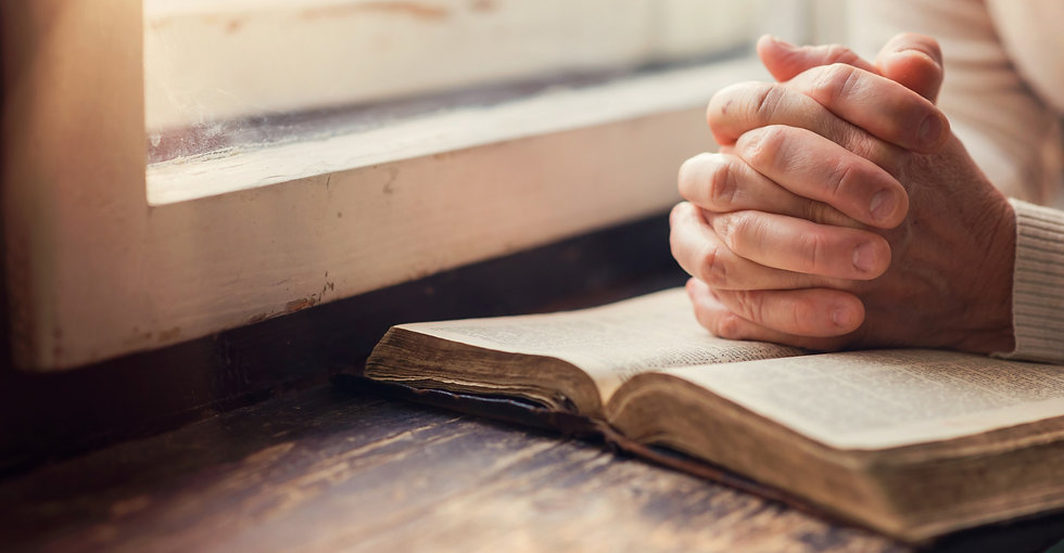 Hands Praying on the Bible