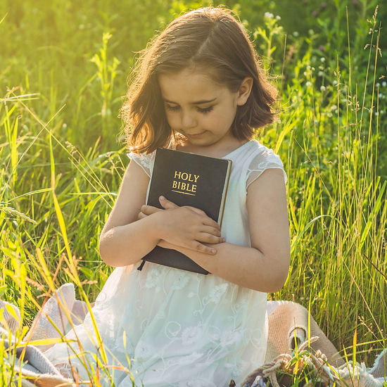 Child Holding The Bible