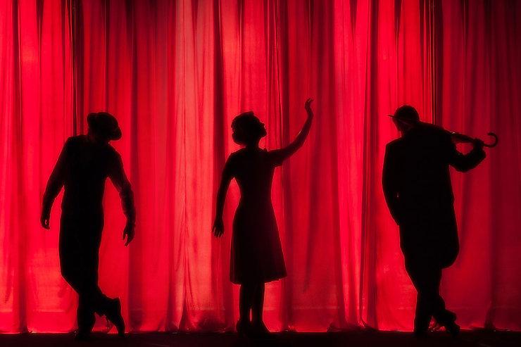 Une photo de théâtre représentatnt des silhouettes noires de trois personnes debouts espacées d'un mètresur un rideau rouge vif. Une silhouette d'homme à gauche avec un chapeau. Tourné de 3 quarts vers nous il porte un chapeau et penche la tête vers le sol avec les bras légèrement écartés. Au centre une femme en robe qui lève un bras au ciel en tournant la tête. A droite un homme de dos en costume qui penche la tête vers la gauche et vers le bas. Il tient un parapluie dans sa main droite qu'il pose sur son épaule.