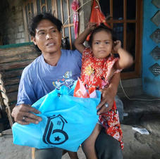 a mother and child outside their house in Buleleng