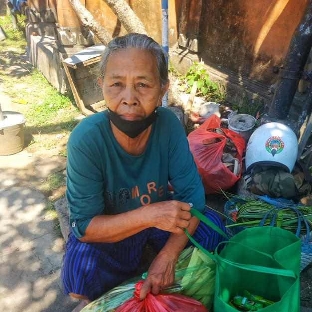 Street vendor in Tabanan receiving a bag of basic food