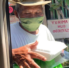 street vendor receiving meal box and Rp. 100.000 food bag